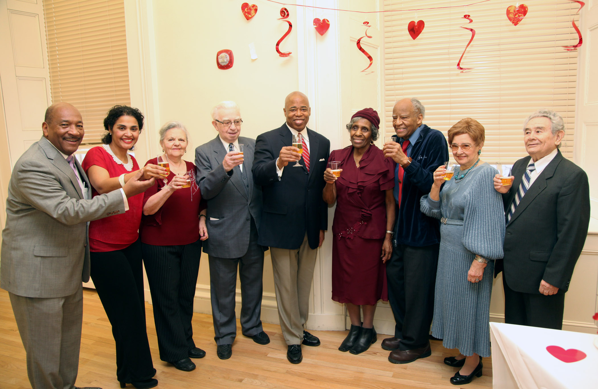 Brooklyn Borough President Eric Adams offers a sparkling cider toast during his Sweethearts celebration in honor of Valentine's Day at Borough Hall; he is joined by (from left to right) HealthFirst Vice President of External Affairs George Hulse and Deputy Brooklyn Borough President Diana Reyna, as well as couples married for 50 years or more. Photo Credit: Kathryn Kirk/Brooklyn BP's Office