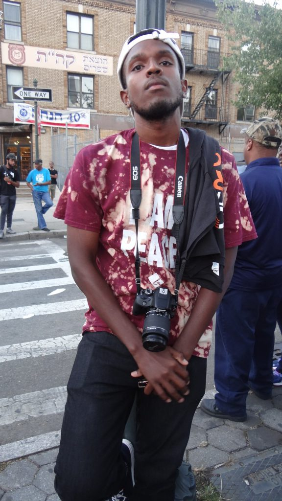 Chris Wise, 23, co-founder of Black Market Wares. We're a youth empowerment agency based out of Ebbets Field Apartments. We seek to expose our youth to new horizons via arts, sports and entrepreneurship. We're out here because this is us! We're peace activists on the block. The fact that the man was shot outside of my apartment complex. The fact that this is what we do as an organization. There was once a movement at one time; there was legitimate activism that happened in this country. But we don't see the activism that happens now, day-to-day, particularly among black youth. So to walk over here and show solidarity and remembrance… part of it is because we just want to live, but another part of it is that this is an opportunity to let the world see us, hear us and know that change is brewing.