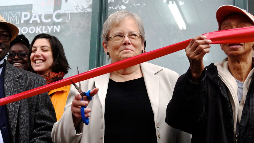 Deb Howard, executive director for the newly named IMPACCT Brooklyn, prepares to cut the ribbon at one of its new storefront offices, located at 1124 Fulton Street