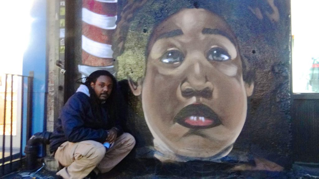 Artist Vince Ballentine stands in front of a mural he just completed of the Notorious B.I.G., located on the corner of Fulton Street and St. James Place
