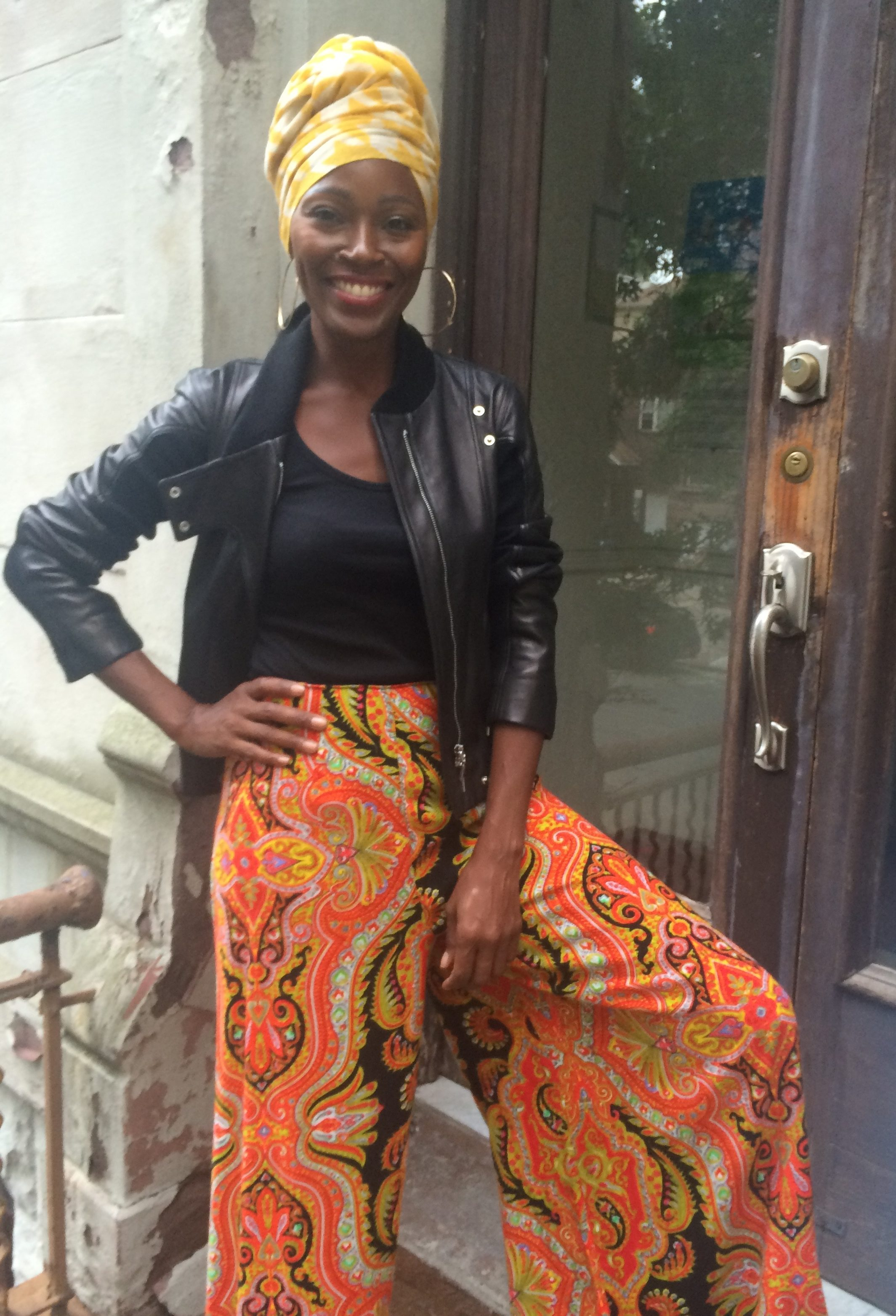 Sheryl Roberts poses in a Indigo Style Vintage ensemble in front of her Greene Ave house. Black leather jacket over a black shirt on top of loose orange patterned trouser skirt